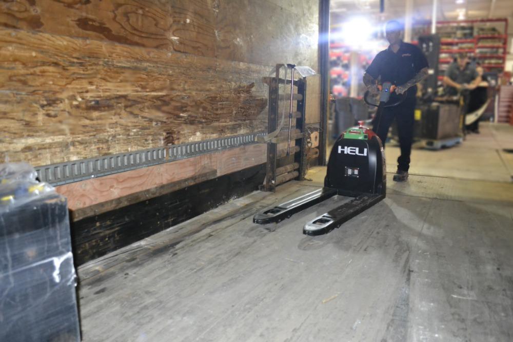 Travailleur entrant dans une remorque avec un transpalette électrique